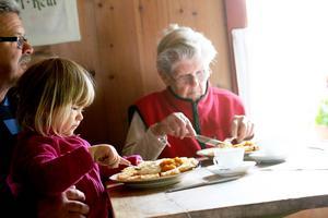 Inez Pertmann äter frasvåffla sittandes i knät på morfar Claus Pertmann. Bredvid sitter mormors mor Karlen Hallquist från Valsjöbyn.