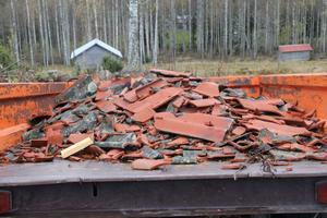 En del av de gamla och skadade tegelpannorna ligger på vagnen för borttransport.
