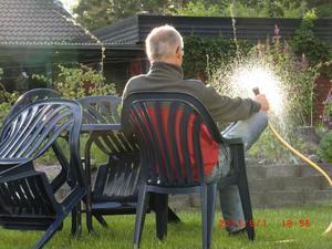 När jag kom ut på verandan fick jag se min make sitta och vattna blommorna. Stackarn han var väl trött och måste sätta sig ner. Tur att det fanns en stol till hands.Jag smög in och hämtade kameran. Hoppas han får se bilden i VLT någon morgon när han äter frukost.