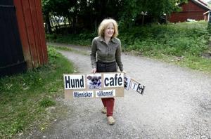 Carin Hughes är på väg för att sätta upp skylten till sitt hund- och trädgårdskafé.