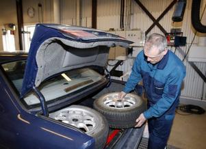 Bilprovaren Patrik Sundberg, kontrollerar att den här bilen har alla däcken med. Eftersom det var så trångt i bakluckan fick två av däcken ligga i baksätet i stället. Foto: Jan Andersson