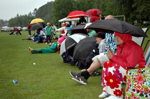 REGNIGT. Föräldrar och släkt satt och kurade under tecken och paraplyer för att hålla sig varm.