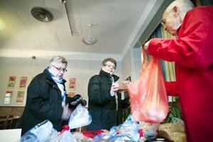 Berit Westling köper bröd hos Björn Bergström, som är ordförande för Röda korset i Enånger.