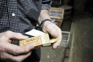 Hans Erik visar upp 100 år gamla cigaretter i originalförpackning.