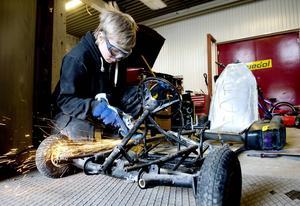 Joel Vesterlund arbetar med ett av verkstadens projekt, en minidragracingbil.