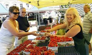 – De var lika fina som sist, men nu är de ju billigare, säger Eva Mattsson som tillsammans med maken Lasse köper en liter jordgubbar av Nancy Åberg på Rådhustorget.
