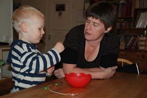 Assar Andersson, 2 år, visar Birgitta Axelsson hur han gör ett pärlhalsband