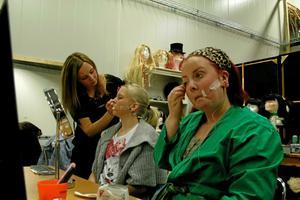 Sminkösen Sara Eriksson ordnar till Alva Edlunds ansikte, medan Sandra Höjer fixar sig själv.