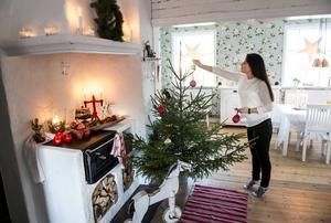Helena Tjernström vid adventsgranen som är enkelt dekorerad. När julen närmar sig får barnen fortsätta pyntandet.