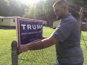 Billy Prater, 27, sätter upp en skylt med Donald Trumps namn på sitt staket i West Virginia, 28 april 2016. Han har varit utan jobb länge sedan kolgruvorna i området började läggas ned. Han tillhör förlorarna i den nya ekonomin.    Claire Galofaro/AP/TT