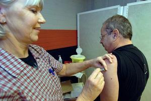 Sjuksköterskan Marie Eriksson delar ut en första dos vaccin.