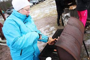 Lina Andersson grillar korv. Hon är vid backen med sin man och deras två barn, samt tre av barnens kompisar.
