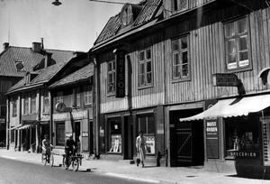 Stora gatan 50-54 så som det såg ut 1956. Norra Källgatan går längst till vänster. Huset närmast i bild kallades Bergholmska gården. Där låg frisör och speceriaffär. Lägg märke till den kraftfulla marknadsföringen av Blixtgyllen från Upsala Ångqvarns AB. Var det havregryn? En trappa upp låg Syster Anikas som kan ha varit en sjukvårdsbutik som tidigare legat i parfymeriet.