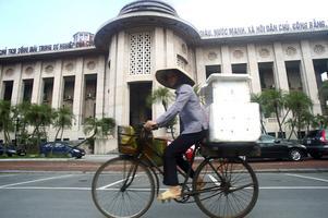 En cyklist passerar Vietnams centralbank i Hanoi.