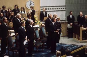 Kung Carl XVI Gustaf talar vid Riksmötets öppnande 1975.  Bakom kungen (t.h.) står prins Bertil (främre raden 3:a fr.v). Närmast i bild (främre raden 1:a fr.v.) står statsminister Olof Palme (S).