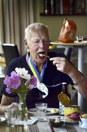 "Runt Olle Drakenbergs hals hänger Laxå fiskakademis symbol. Piscis bona betyder naturligtvis ""fina fisken""."