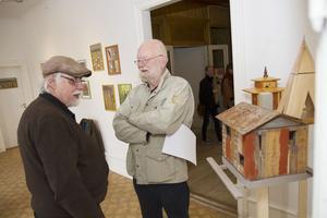 Thomas Tidholm visar upp sina fågelhus för bildkonstnären Ola Granath.