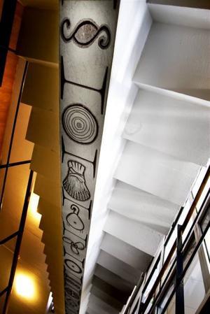 SymboliskT.  Utsmyckningen med tecken för olika yrken och branscher löper under trappstegen. Konstnär  okänd.