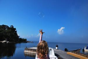Vinnarbilden. Ylva-Li jagar en såpbubbla.
