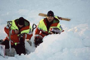 Två fjällräddare gräver fram en tjej som låg begravd under snön.
