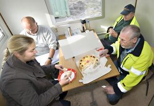 Anläggningsarbetaren Bernt Jonsson och grävmaskinisten Bengt Åberg firar med tårta tillsammans med gatuchefen Ylva Jedebäck Lindberg och arbetsledaren Olle Pettersson.