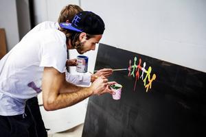 Emir Smajic är koncentrerad när han målar människor som står hand i hand.