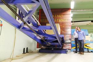 Vagnen med testlådan far ner och landar med en ljudlig smäll mot väggen. Hans Persson och Pontus Eding följer hela händelseförloppet, från det att stålställningen höjs upp automatiskt tills att vagnen far i väggen. På så sätt kan man testa hur bra lådan klarar sidostötar.