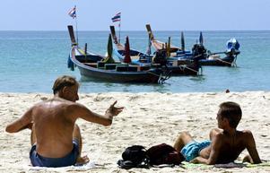 Turister njuter av solen på stranden Kata beach på Phuket.