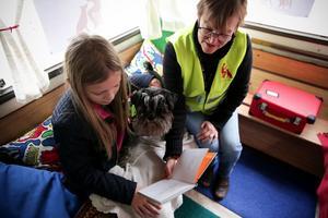 Tanken är att läshunden ska ligga i elevens knä medan lästräningen pågår. Just här tycks dock hunden Ester vara intresserad av någonting helt annat.