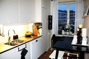 Köket är ganska litet men mysigt med ljus, växter och frukt.