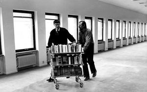 Stadsbiblioteket i Västerås 1983, till höger Lars-Gunnar Larsson. vaktmästare och Jan Nilsson, stadsbibliotekarie som kämpar med en bokvagn.