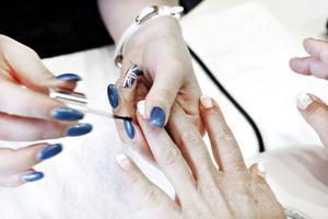 Nu är det dags att dekorera naglarna. Tre vita prickar omformas med millimeterprecision till sommarblommor. Amanda själv har blå naglar med brittiska flaggan på en av dem.
