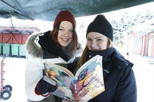 Mikaela Jansson och Carolina Larsson kollar kokboken.