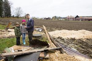 Tomas Näslund med barnen Anton och Signe tittar på brandresterna. I bakgrunden syns Per Göranssons hus.