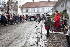 Selma Weiss sjön Tänd ett ljus ackompanjerad av mamma Ellen och lillebror Alfred Weiss när den 24:e och sista lyckan i Gävles levande julkalender öppnades i Gamla Gefle. Ett hundratal Gävleborg hade samlats för att lyssna.