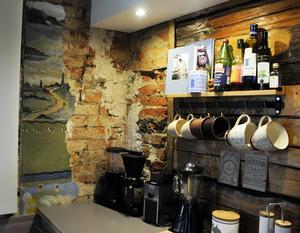 I köket syns både timmervägg, tegel och en gammal väggmålning som kom fram under renoveringsarbetet.