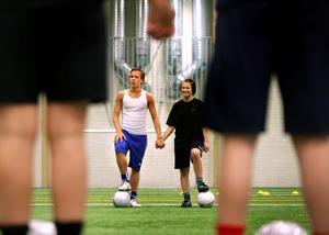 Daniel Andersson håller Lina Ohlsson i handen under en övning på sista träningen för terminen på fotbollsgymnasiet i Timrå, där Lina precis har gått ut första året. Nu är det sommarlov men Lina tränar och spelar både i division III och IV med Söråkers FF.
