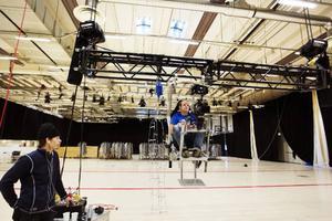 Janne Carlsson provsitter stolen där en av filmarna ska sitta upphissad i taket och bevaka scenen.