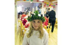 Victoria Hellgren, 11 år, sjunger klart och säkert. Efteråt är hon nöjd med Luciatåget.-- Men det kliar under kronan. Och då börjar strumbyxorna också att klia.Foto: KARIN SUNDIN