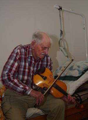 Kan än. Fast han har ont i högerarmen tar han fram fiolen och spelar en låt när MT besöker honom. – Det går lättare att spela om jag håller fiolen mot bröstet i stället för mot hakan, säger han. Men, hörapparaten gör att det skräller så obeskrivligt när jag spelar. Foto:Björn Rehnström