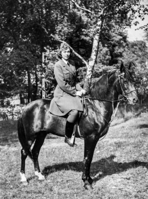 Jane Horney i uniform sittandes på hästryggen på en svart häst under beredskapen under andra världskriget troligen 1940.   Foto: Bertil Norberg / TT