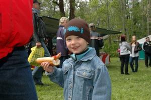 """HUNGRIG. Ville Rollén-Edin, 3 år, Karlholmsbruk, kalasade på en korv. Pappa Pelle Edin spanade efter """"återvändare"""" till samhället."""