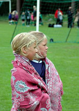 FRYSER. Milly Berggren och Wilma Lindkvist, Östervåla-Hinden, värmer sig på avbytarplats.