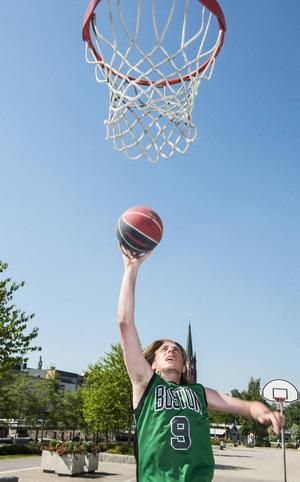 Anton Svedin spelar basket för sig själv i den 30-gradiga värmen på streetbasketplanen.