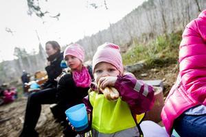 Freya Jonsson njuter av en varmkorv i skogen.
