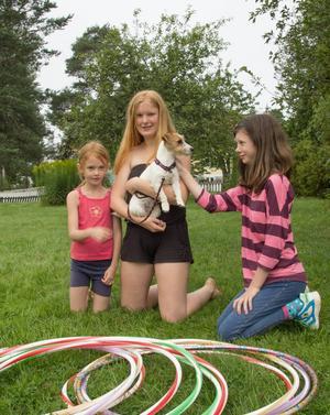 Systrarna Michelle, Melody och Melinda tar en danspaus och gosar med valpen Annie.