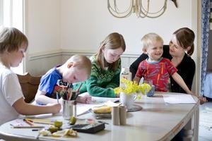 Ritdag i köket. Bo, 5 år, Albin, 6 år, och Matilda, 8 år, är koncentrerade vid köksbordet medan lille Gunnar, 3 år, och mamma Anna Forslund har något annat i blicken.