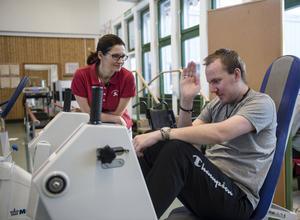 Sjukgymnasten Helen Eriksson hjälper Henric med styrketräningen.