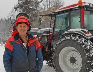 Anders Eriksson hugger ved i de branta Reseleniporna. Utan rädsla tar han sig utför branterna med traktorn.