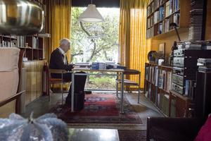 Arkitekten Jack i arbete vid sitt arbetsbord i arbetsrummet.